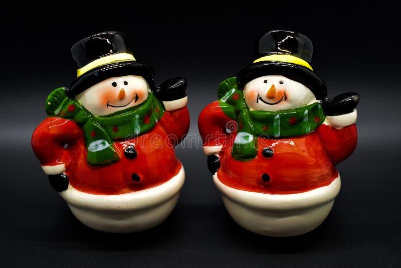 Estatuetas feitos a mão dos bonecos de neve isoladas no fundo preto Decoração do Natal fotos de stock
