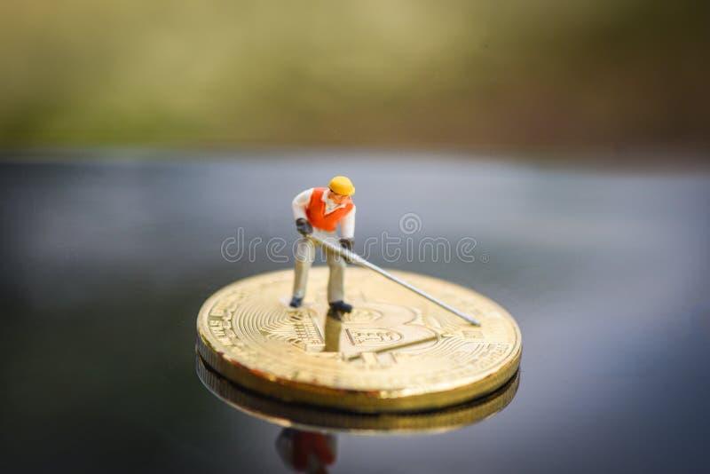Estatuetas que trabalham do bitcoin virtual do cryptocurrency de Bitcoin o conceito de mineração de escavação dourado de mineraçã fotos de stock