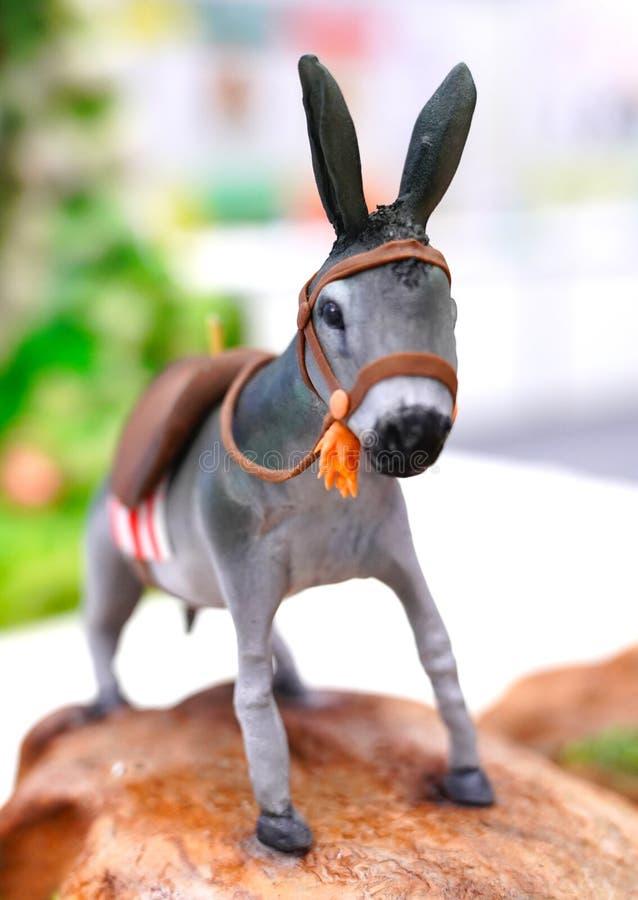 Estatuilla decorativa y colorida minúscula de un burro imagenes de archivo