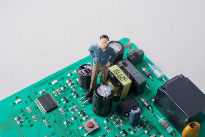 Estatuilla minúscula del modelo de los hombres en placa de circuito fotografía de archivo libre de regalías