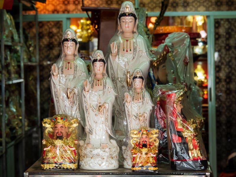 Estatuillas de la diosa de la misericordia, de Guan Yin y de dios de la fortuna, Cai Shen, en una tienda de los art?culos del rez imagenes de archivo