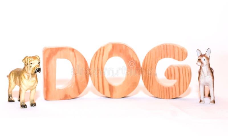 Estatuillas de los perros y del perro de la inscripción en letras de madera fotos de archivo