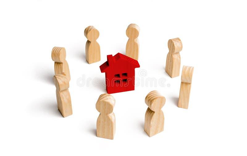 Estatuillas de madera del soporte de la gente alrededor de la casa imágenes de archivo libres de regalías