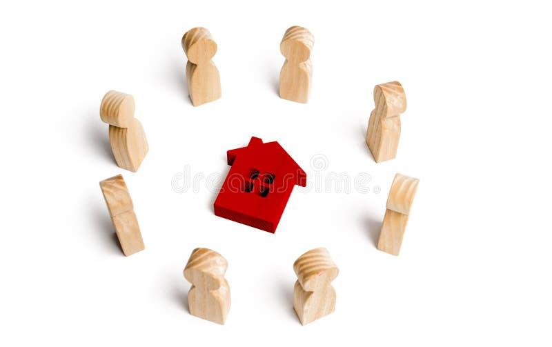 Estatuillas de madera del soporte de la gente alrededor de la casa Búsqueda para un nuevo hogar y las propiedades inmobiliarias C fotos de archivo libres de regalías