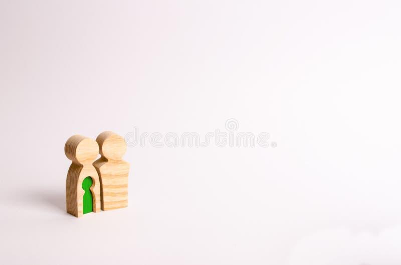 Estatuillas de madera de una familia joven en un fondo blanco Concepto de una pareja casada fuerte y sana joven Un par cariñoso fotos de archivo