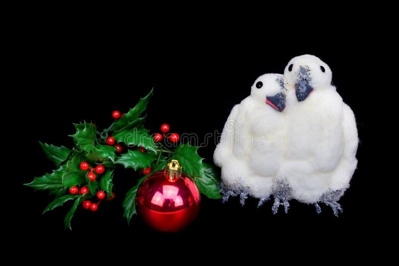 Estatuillas del pingüino con las bayas rojas de la bola y del acebo de la Navidad foto de archivo libre de regalías