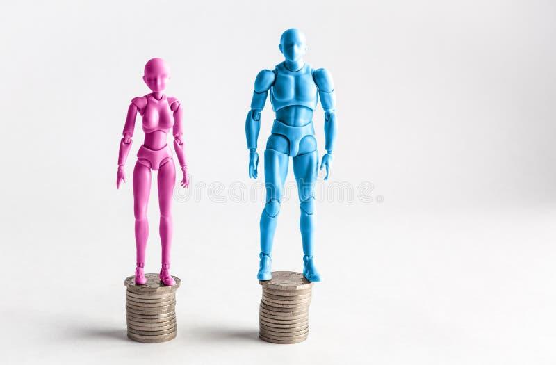 Estatuillas masculinas y femeninas que se colocan al lado de pilas iguales de monedas fotos de archivo