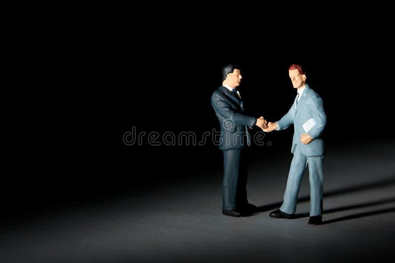 Estatuillas miniatura de los hombres de negocios del apretón de manos imagen de archivo