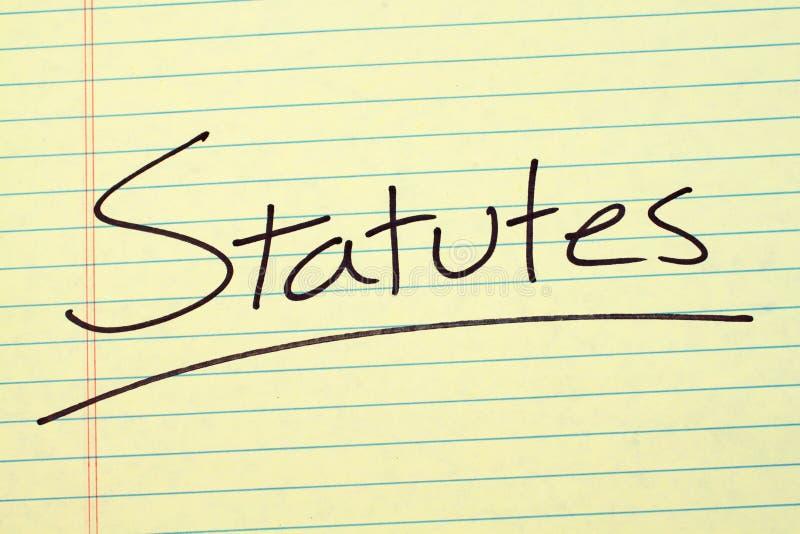 Estatutos en un cojín legal amarillo imagenes de archivo
