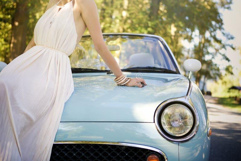 Este é um retrato de uma mulher que senta-se na capa de seu carro do vintage fotos de stock royalty free
