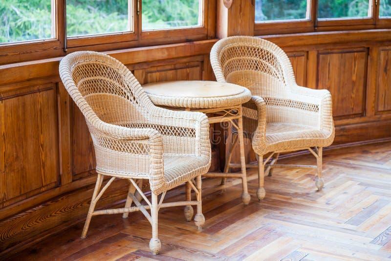 Este par de las sillas italianas del wickler con la tabla es parte de los muebles originales 1910-1920 de un chalet semi-abandona foto de archivo
