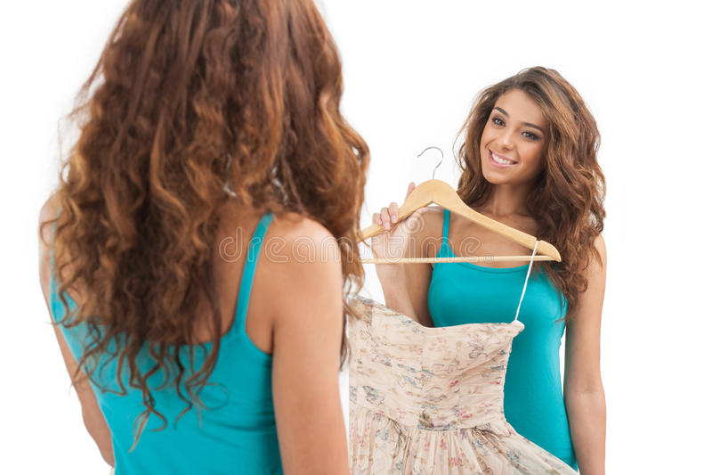 Este vestido es perfecto. Mujeres jovenes hermosas que sostienen un vestido y imágenes de archivo libres de regalías