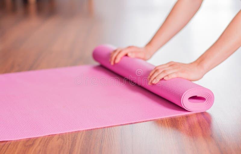 Esteira de dobramento da ioga ou da aptidão da mulher das mãos após o exercício em casa fotografia de stock