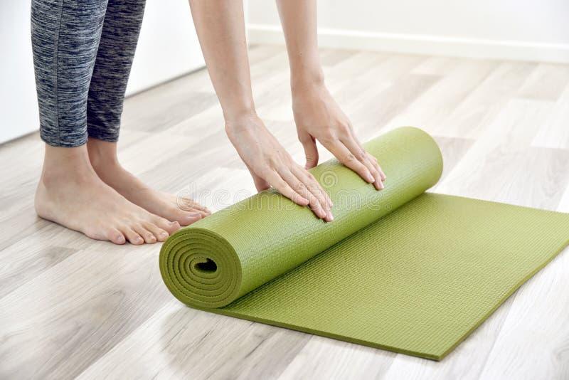 Esteira de dobramento da ioga ou da aptidão da mulher após dar certo em casa, Hom fotografia de stock