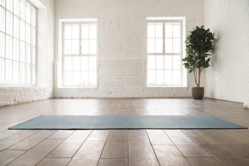 Esteira desenrolada da ioga no assoalho de madeira no estúdio da ioga fotos de stock
