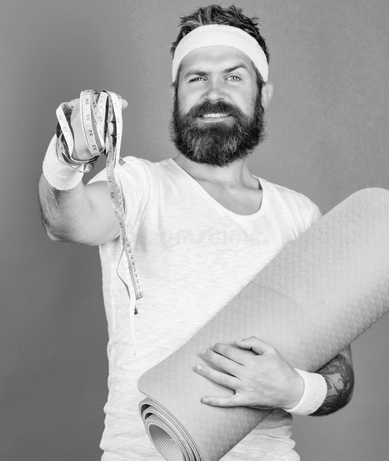 Esteira farpada e fita m?trica da aptid?o da posse do atleta do homem Estada do guia do atleta na forma Conceito da gin?stica aer foto de stock