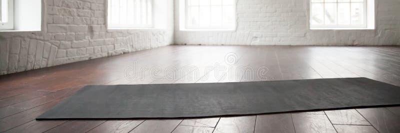 Esteira horizontal da ioga da foto no assoalho de madeira no clube de esporte imagem de stock royalty free