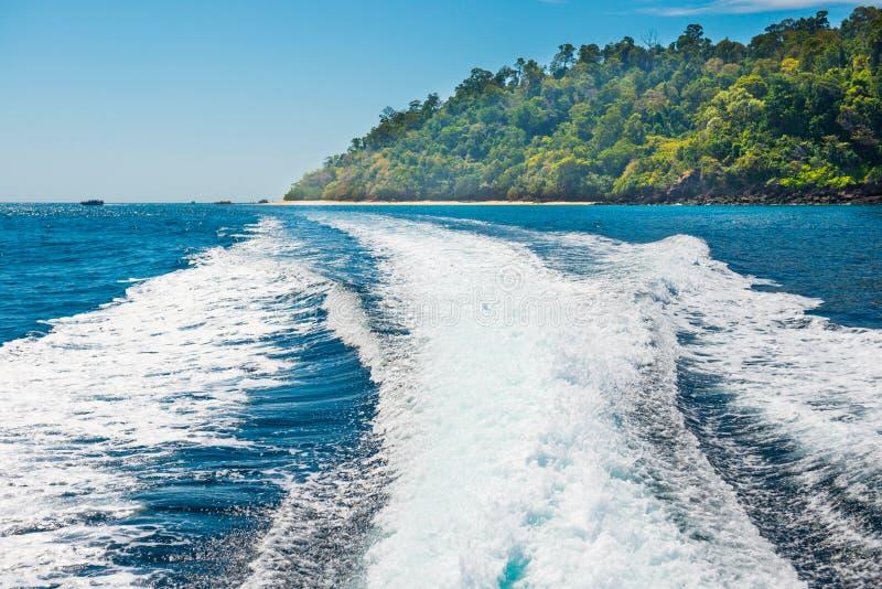 Estela del barco en superficie del agua al lado de la costa de la isla fotografía de archivo