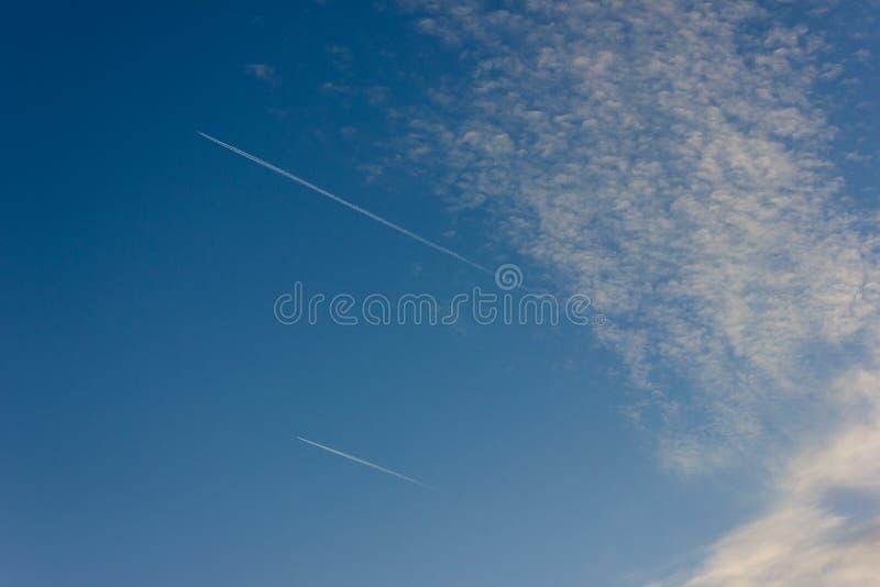 estelas de vapor del jet en puesta del sol del cielo azul en el campo alemán del sur imágenes de archivo libres de regalías