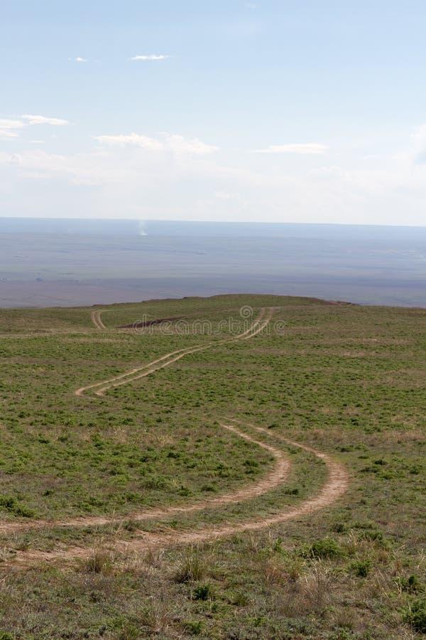Estepe de Cazaquist?o com estradas de terra do rolamento fotografia de stock