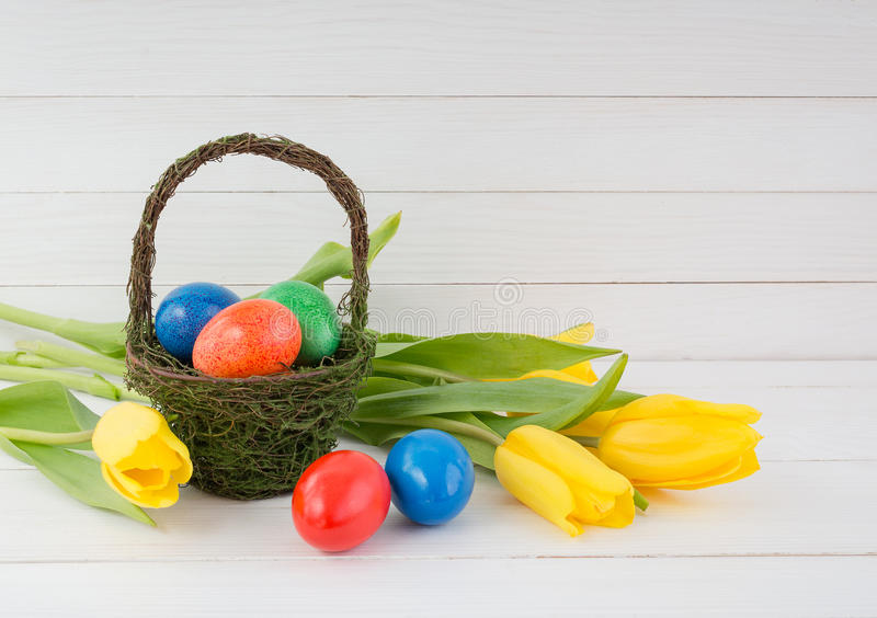 Ester eggs in basket and yellow tulips on white wooden background stock image