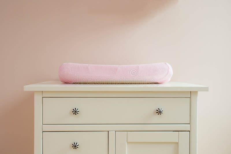 Estera cambiante en el diseño moderno del sitio del bebé, colores rosados fotos de archivo
