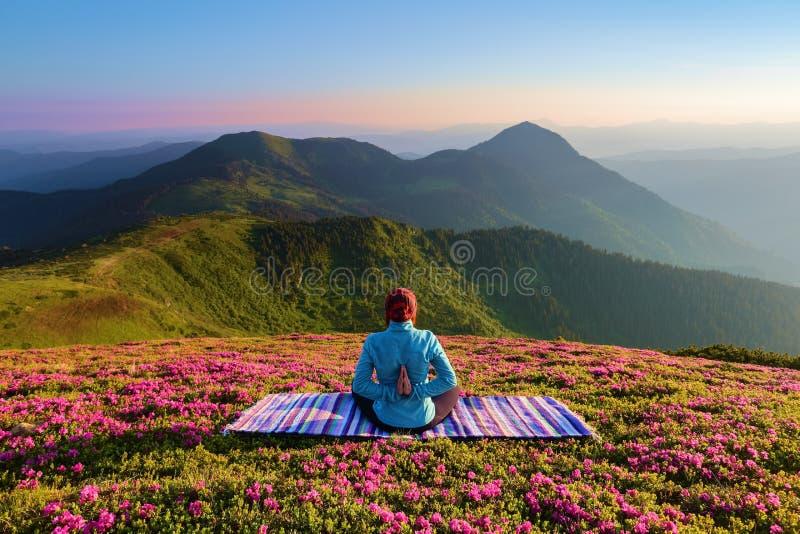 Estera colorida La muchacha de la yoga en la actitud del loto El césped con las flores del rododendro Altas montañas Verano mágic foto de archivo