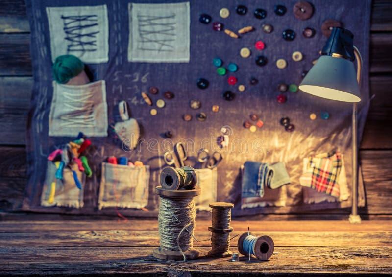Estera de costura hecha de hilos, de agujas y de botones en taller del sastre stock de ilustración