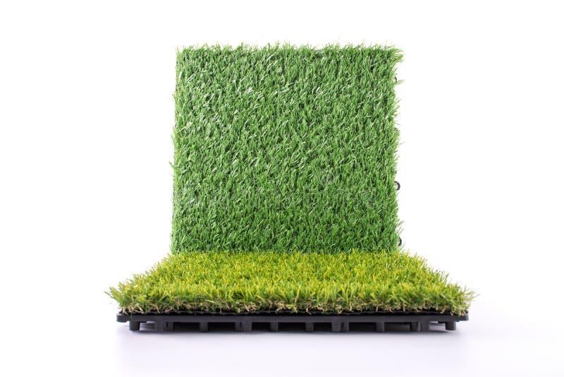 Estera de la hierba en el fondo blanco Fondo artificial de la teja del c?sped Concepto del objeto y del fondo fotografía de archivo libre de regalías