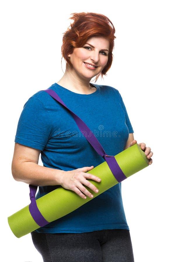 Estera de la yoga de la mujer que lleva Curvy imagen de archivo libre de regalías