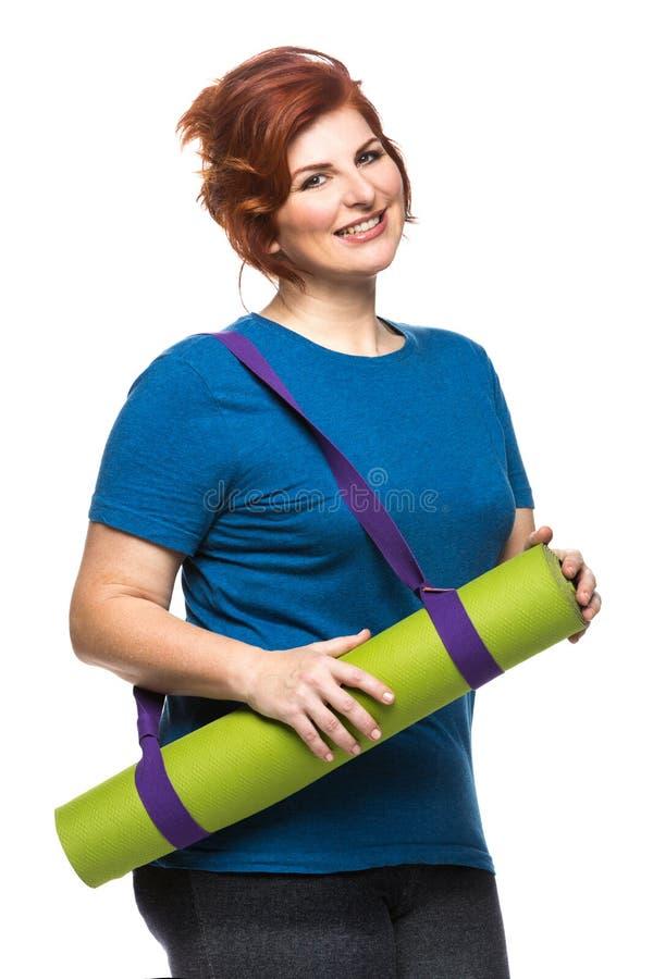 Estera de la yoga de la mujer que lleva Curvy imagen de archivo