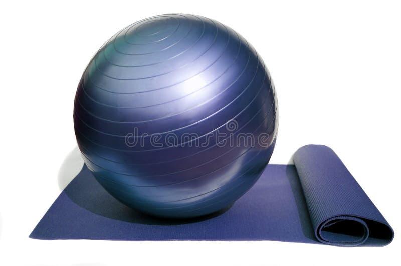 Estera y bola de la yoga foto de archivo