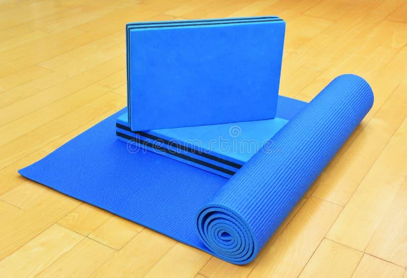 Estera y ladrillos azules del ejercicio para la yoga o Pilates imágenes de archivo libres de regalías