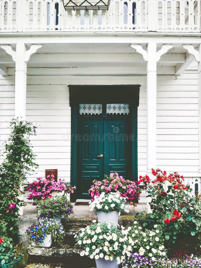 Esterno accogliente della casa di campagna di entrata del terrazzo di legno bianco della porta con i fiori fotografie stock libere da diritti