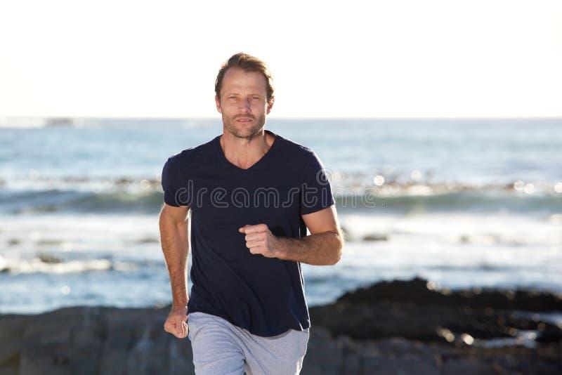 Esterno corrente dell'uomo bello dalla spiaggia fotografia stock