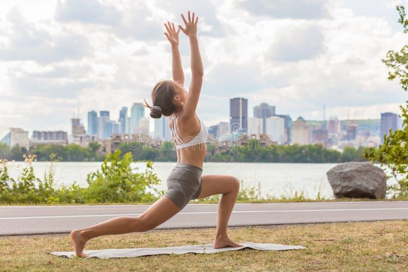 Esterno della classe di benessere di yoga nella donna del parco della città che fa posa crescente di alto affondo sulla stuoia di fotografia stock libera da diritti