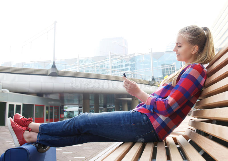 Esterno di seduta sorridente della donna di viaggio che esamina telefono cellulare immagini stock libere da diritti