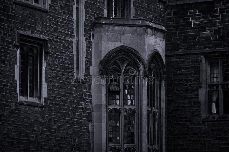 Esterno di vecchia costruzione gotica con le pareti di pietra ed il bovindo nel crepuscolo uguagliante fotografia stock libera da diritti