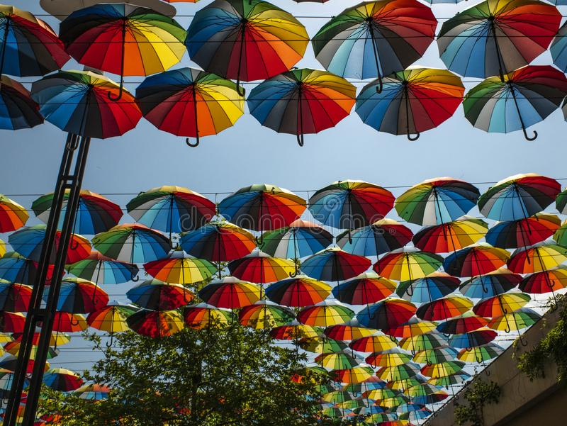 Esterno variopinto degli ombrelli come decorazione ombrelli dei colori differenti contro il cielo ed il sole fotografia stock libera da diritti