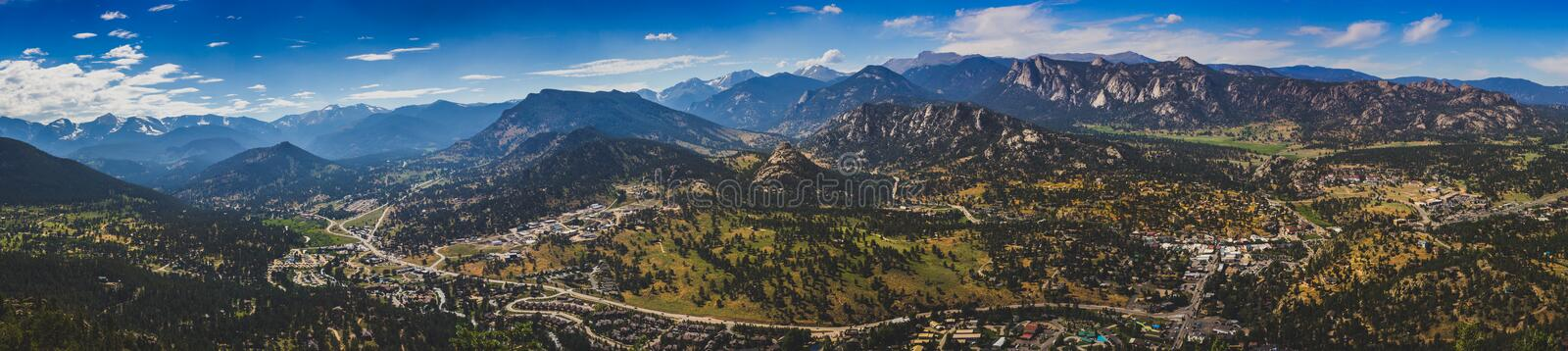 Estes Park Aerial Panorama. Scenic valley and snow-covered peaks under a blue sky with clouds in Estes Park, Colorado near the Rocky Mountain National Park royalty free stock image