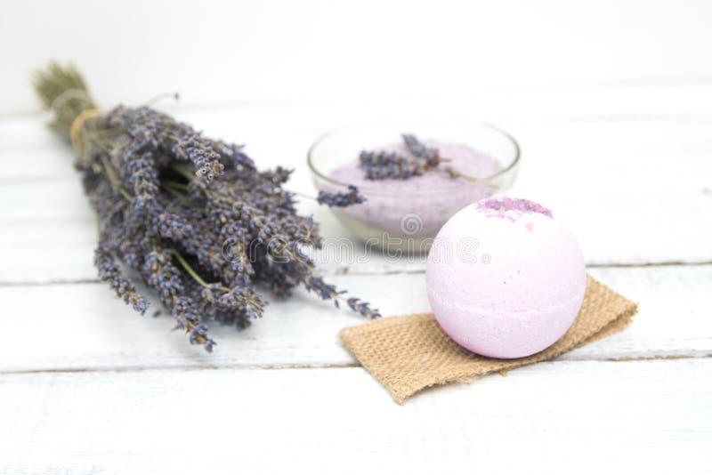 Estetiche naturali Bombe fatte a mano del bagno della lavanda e fiori della lavanda sulle plance di legno bianche immagine stock