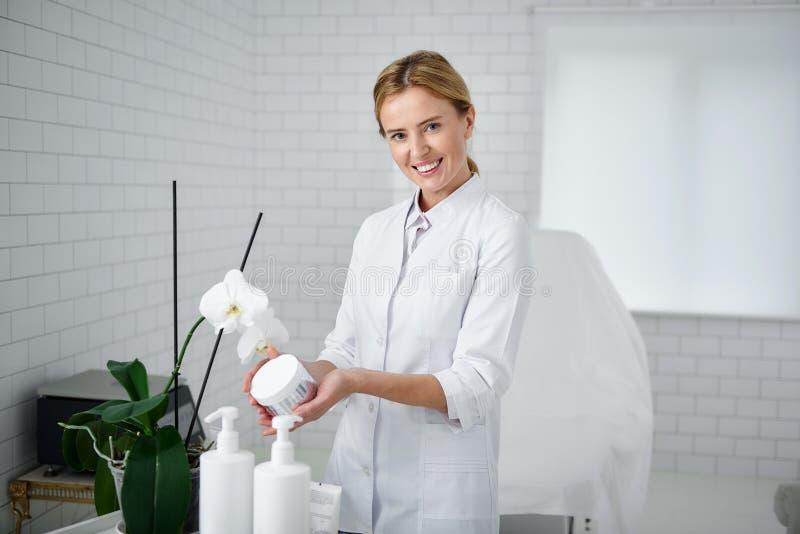 Esteticista alegre que guarda o produto cosmético dos cuidados com a pele fotos de stock royalty free