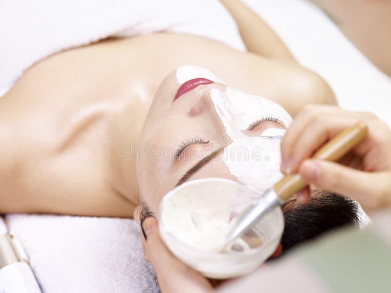 Esteticista asiático que aplica a máscara facial na cara da jovem mulher fotos de stock royalty free