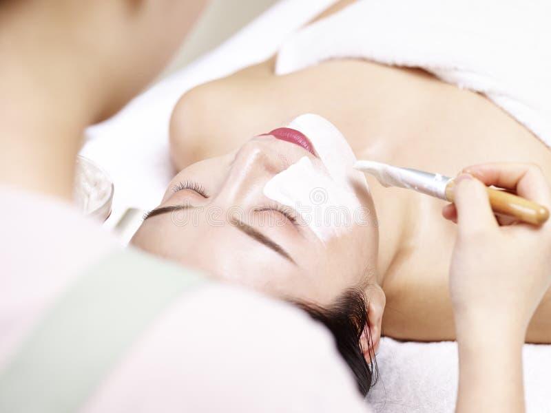 Esteticista asiático que aplica a máscara facial na cara da jovem mulher imagens de stock royalty free