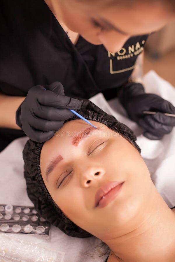 Esteticista fêmea novo que aplica o tratamento da pele após o procedimento da remoção da tatuagem da sobrancelha imagem de stock royalty free