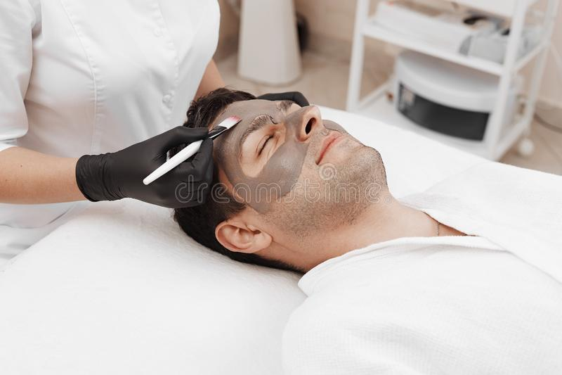Esteticista que aplica a máscara cosmética na cara do homem no salão de beleza dos termas fotos de stock