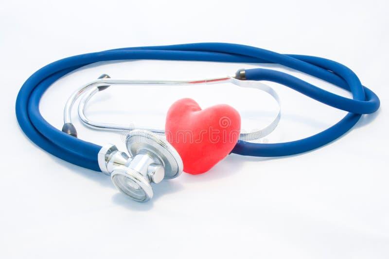 Estetoscópio azul e mentira vermelha do coração no fundo homogêneo branco Foto do conceito da saúde ou da condição patológica do  imagens de stock