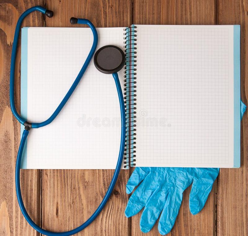 Estetoscópio, bloco de notas da página vazia e luvas na tabela do doutor Diagnóstico médico ou modelo da prescrição do doutor imagem de stock royalty free