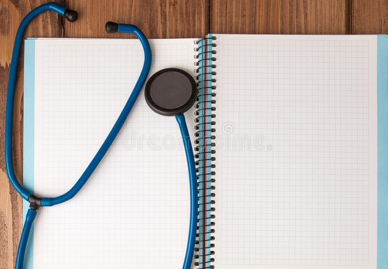 Estetoscópio, bloco de notas da página vazia na tabela do doutor Diagnóstico médico ou modelo da prescrição do doutor fotografia de stock royalty free