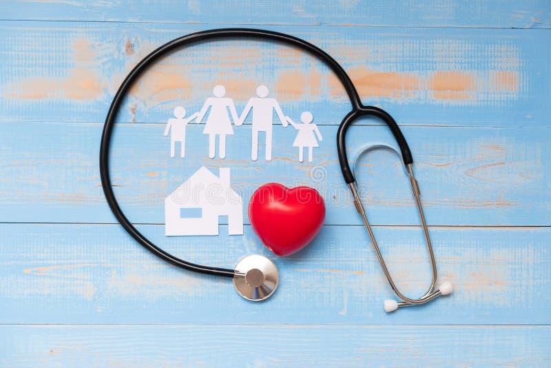 Estetoscópio com forma vermelha do coração, papel da família e da casa na cor pastel azul de madeira fotos de stock